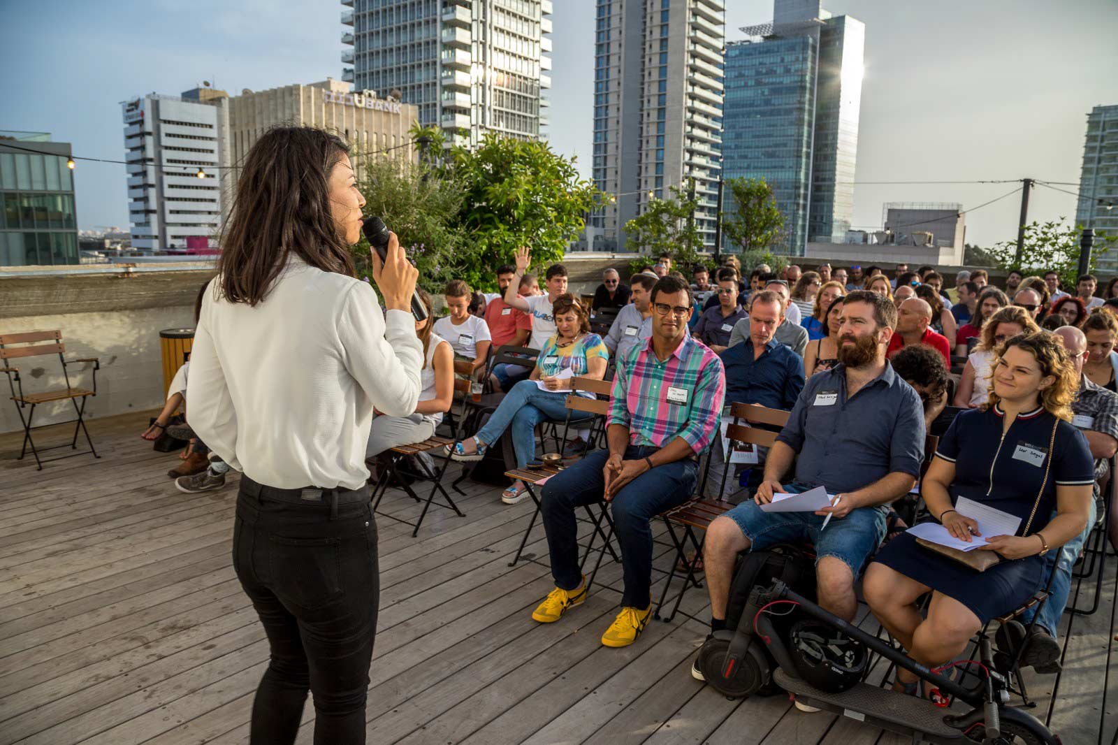 Dana zelicha OWBA founder at a rooftop speaking event in front of a large audience